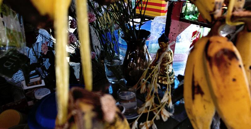 ミニマートに祀られている仏像と花
